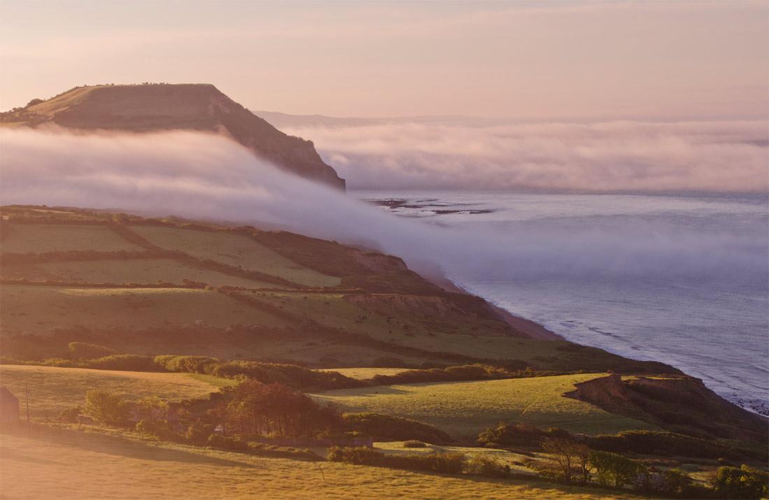 Mist cascading around Golden Cap.